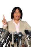 Mulher que fala atrás dos microfones Fotografia de Stock Royalty Free