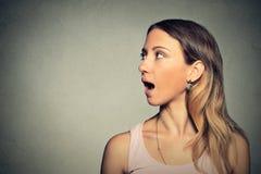 Mulher que fala com o som que sai de sua boca aberta fotografia de stock