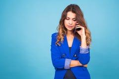 Mulher que fala em seu telefone celular sobre um fundo azul foto de stock