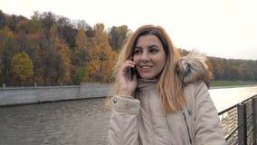 Mulher que fala na navigação do telefone no barco no rio perto de Autumn Park colorido vídeos de arquivo