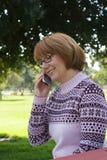 Mulher que fala na pilha no parque Fotos de Stock Royalty Free