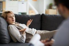 Mulher que fala no sofá fotos de stock