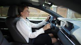Mulher que fala no speakerphone do em-carro ao conduzir filme