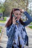 Mulher que fala no telefone ao andar imagem de stock royalty free