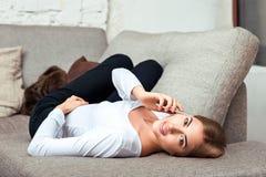 Mulher que fala no telefone celular que encontra-se no sofá imagem de stock royalty free
