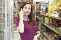 Mulher que fala no telefone celular no supermercado imagem de stock
