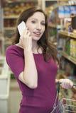 Mulher que fala no telefone celular no supermercado fotos de stock royalty free