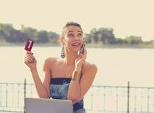 Mulher que fala no telefone celular que guarda o cartão e o portátil de crédito fotografia de stock royalty free