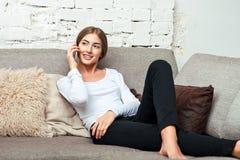 Mulher que fala no telefone celular que senta-se no sofá Imagem de Stock Royalty Free
