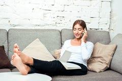 Mulher que fala no telefone celular que senta-se no sofá Imagens de Stock Royalty Free