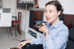 Mulher que fala no telefone com o assistente da voz digital imagem de stock royalty free
