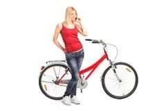 Mulher que fala no telefone e na posição por uma bicicleta Fotografia de Stock Royalty Free
