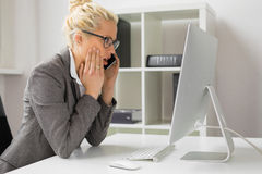 Mulher que fala no telefone e que olha o computador em choque fotografia de stock royalty free