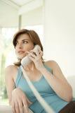 Mulher que fala no telefone em casa Fotos de Stock Royalty Free