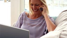 Mulher que fala no telefone em casa video estoque