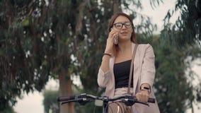 Mulher que fala no telefone em um passeio da bicicleta video estoque