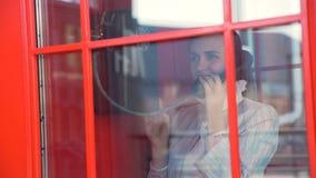 Mulher que fala no telefone na cabine de telefone video estoque