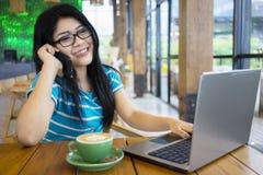 Mulher que fala no telefone no café Foto de Stock