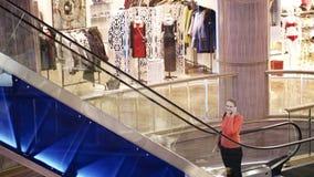Mulher que fala no telefone no centro de compra. filme