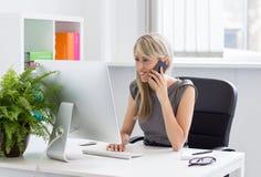 Mulher que fala no telefone no escritório imagem de stock