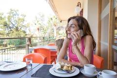Mulher que fala no telefone no terraço do café Imagem de Stock