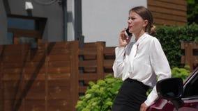 Mulher que fala no telefone no pátio perto do carro video estoque