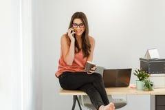 Mulher que fala no telefone que toma uma ruptura de café Fotografia de Stock Royalty Free