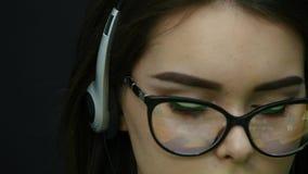 Mulher que fala nos auriculares em um escritório video estoque