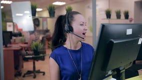 Mulher que fala nos auriculares em um escritório limpo brilhante, centro de atendimento de Frendly video estoque