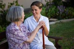 Mulher que fala para medicar ao sentar-se no banco no parque Fotos de Stock Royalty Free