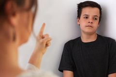 Mulher que fala seu filho do adolescente que escuta com expres furados imagem de stock