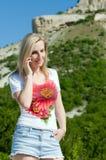 Mulher que fala sobre o telefone nas montanhas Foto de Stock