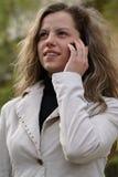 Mulher que fala a um telefone de pilha Foto de Stock Royalty Free