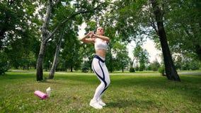 A mulher que faz a aptidão exercita exterior Corredor fêmea que estica antes de maratona running na menina magro da floresta verd filme