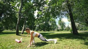 A mulher que faz a aptidão exercita exterior Corredor fêmea que estica antes de maratona running na menina magro da floresta verd video estoque