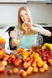 Mulher que faz bebidas dos frutos Fotos de Stock