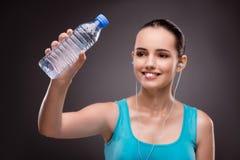 A mulher que faz esportes com a garrafa da água fresca imagem de stock