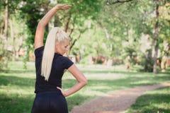 Mulher que faz esticando exercícios para os braços Foto de Stock Royalty Free