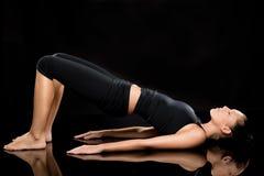 Mulher que faz esticando o exercício no assoalho Imagem de Stock Royalty Free