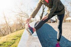 Mulher que faz esticando os pés no parque em uma manhã ensolarada Imagens de Stock