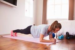 Mulher que faz exercícios da aptidão em Mat In Bedroom fotografia de stock royalty free