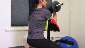 Mulher que faz exercícios da aptidão para a opinião traseira do bíceps vídeos de arquivo