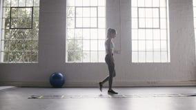 Mulher que faz exercícios da broca da escada da agilidade da velocidade no estúdio da aptidão video estoque