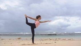 Mulher que faz exercícios da ioga Menina que treina a pose da curva do STD na costa do oceano em Bali video estoque