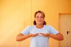 Mulher que faz exercícios de respiração Imagens de Stock