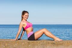 Mulher que faz exercícios dos esportes fora pelo beira-mar Fotografia de Stock