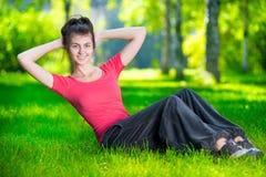 Mulher que faz exercícios para os músculos abdominais imagem de stock