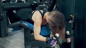 Mulher que faz exercícios para os pés e os músculos das nádegas no gym video estoque