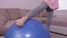 Mulher que faz exercícios para os pés na bola da aptidão vídeos de arquivo
