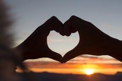 A mulher que faz a forma do coração durante a elevação do sol, deus é conceito do amor, forma do coração, turismo da montanha, sí imagem de stock